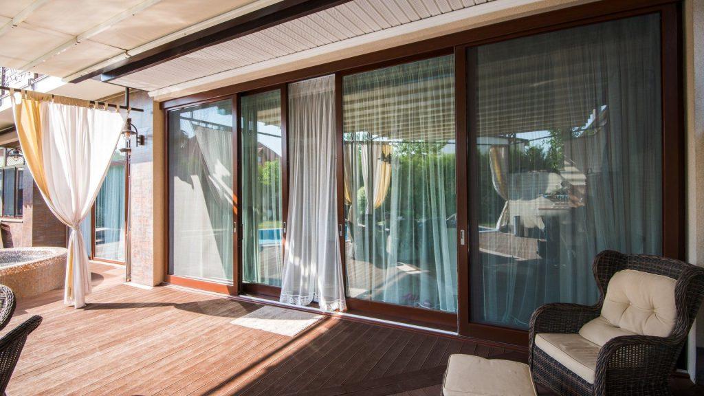 Стеклянные раздвижные двери, обрамленные массивом дерева